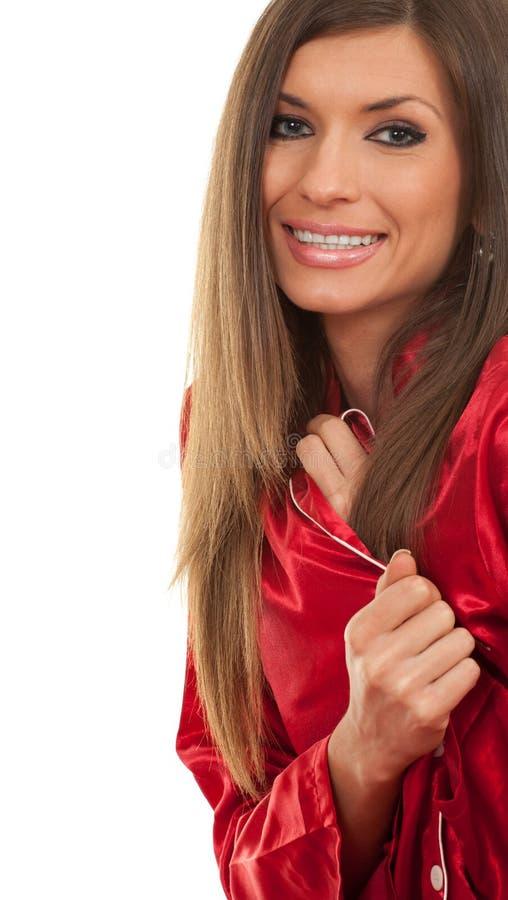 Giovane donna sorridente in pigiami rossi immagine stock libera da diritti