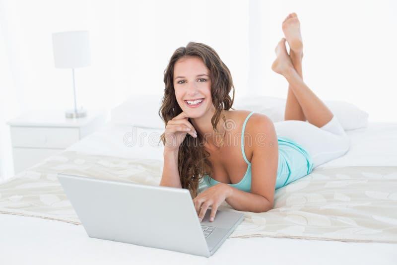 Giovane donna sorridente rilassata che per mezzo del computer portatile a letto fotografie stock libere da diritti