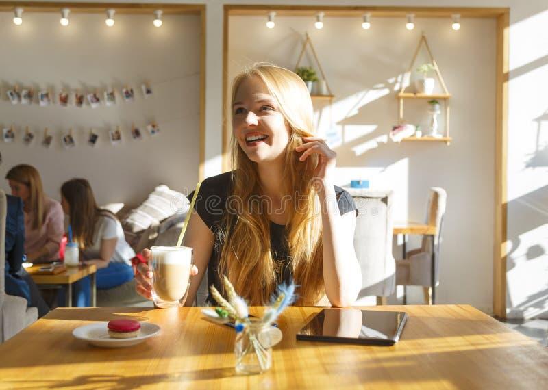 Giovane donna sorridente splendida che esamina diritto la macchina fotografica mentre bevendo caffè e mangiando dolce in caffè fotografia stock
