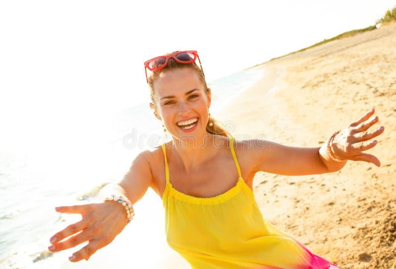 Giovane donna sorridente sulla spiaggia nella sera divertendosi tempo immagini stock libere da diritti