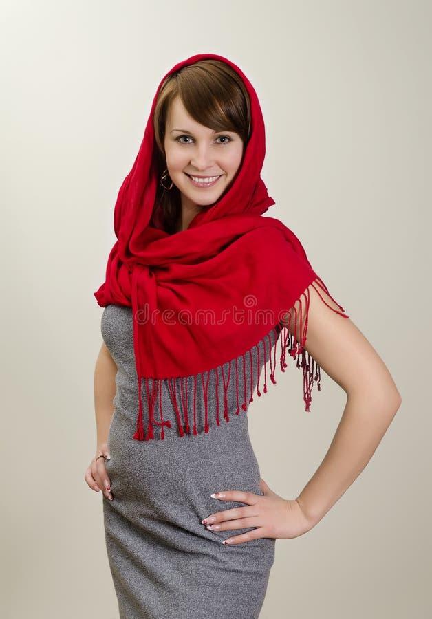 Giovane donna sorridente in una sciarpa rossa. fotografie stock