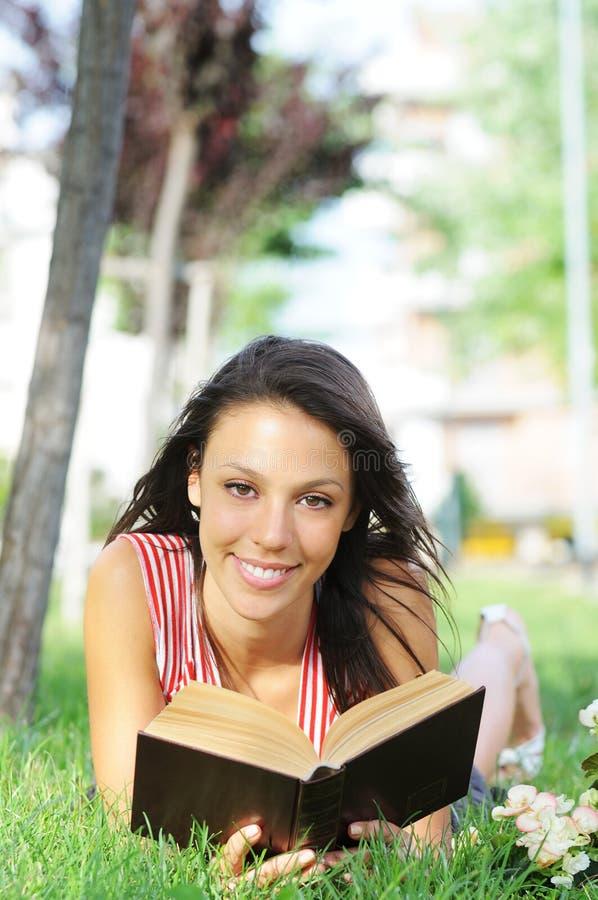 Giovane donna in sosta, in libro e nella lettura verdi fotografia stock libera da diritti
