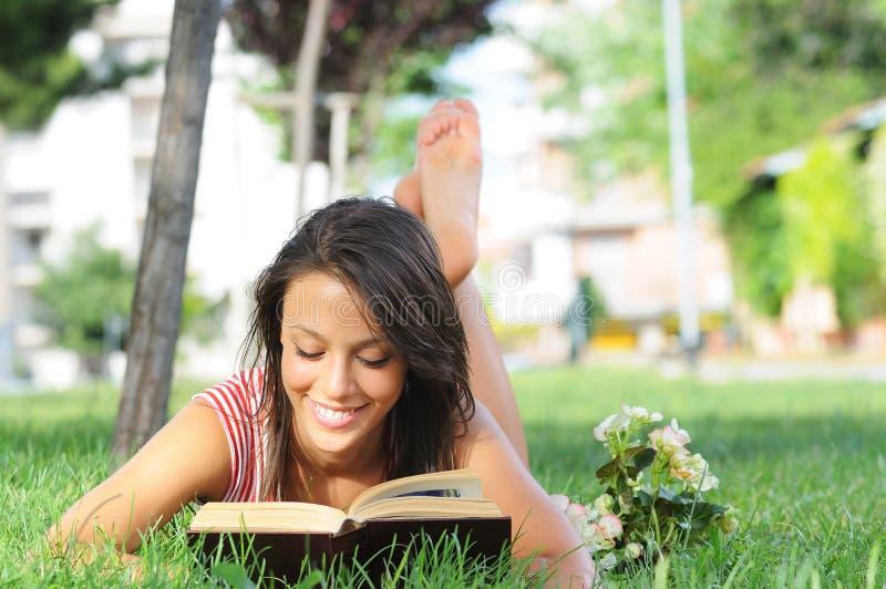 Giovane donna in sosta, in libro e nella lettura verdi fotografia stock