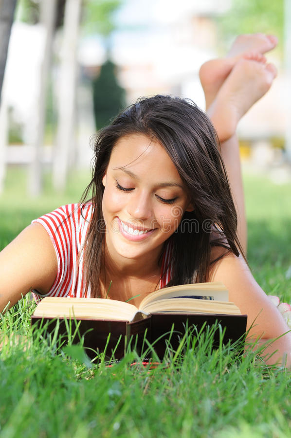 Giovane donna in sosta, in libro e nella lettura verdi immagini stock libere da diritti