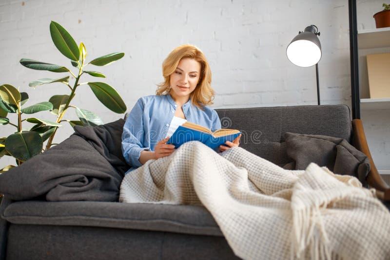 Giovane donna sotto un libro di lettura generale sullo strato fotografia stock libera da diritti