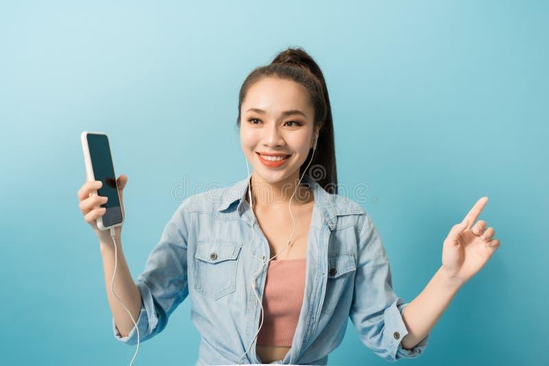 Giovane donna spensierata felice che balla e che ascolta la musica dallo smartphone sopra fondo blu immagine stock