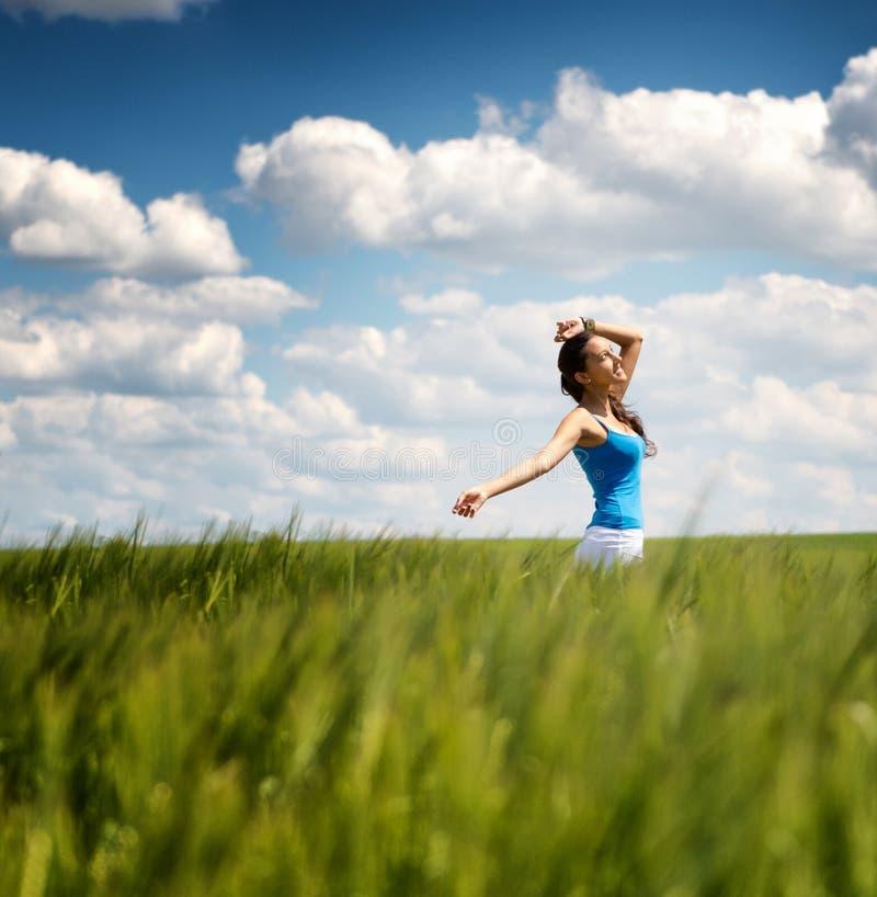 Giovane donna spensierata felice in un giacimento di grano verde fotografia stock