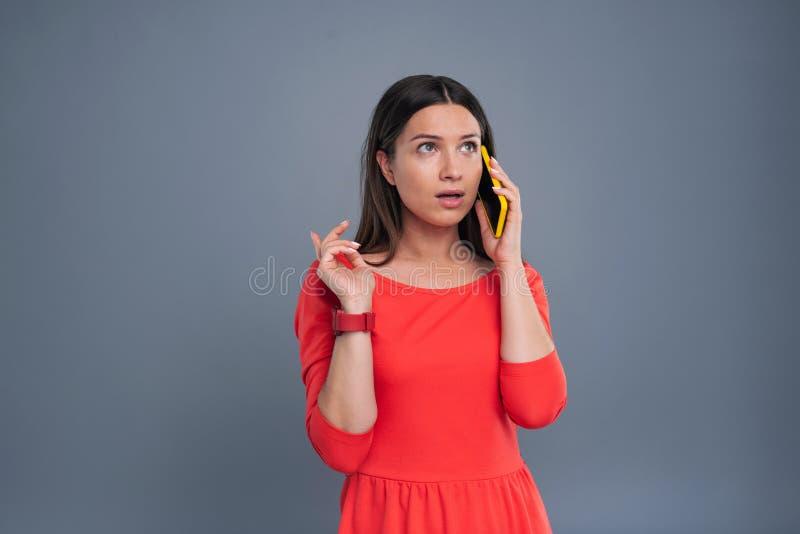 Giovane donna splendida che fa ordine tramite telefono immagine stock