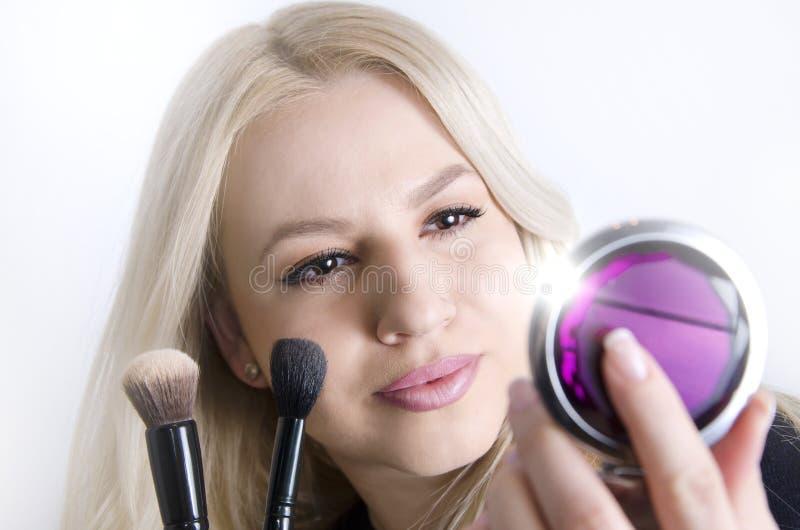 Giovane donna splendida che guarda in specchio mentre mettendo sul trucco fotografie stock libere da diritti