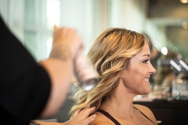 Giovane donna splendida che ottiene capelli disegnati con lacca per capelli fotografie stock