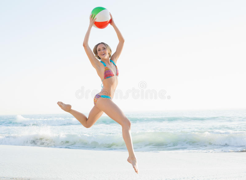 Giovane donna splendida che salta sulla spiaggia che tiene un beach ball fotografie stock libere da diritti