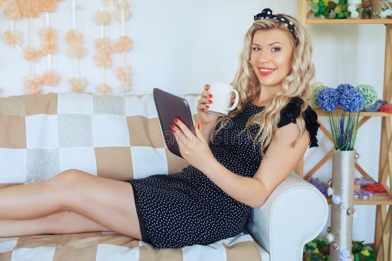 Giovane donna splendida che si trova sullo strato con una compressa e una tazza fotografie stock