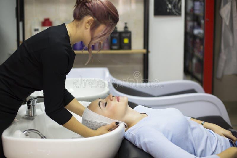 Giovane donna splendida che sorride mentre parrucchiere professionista che avvolge i suoi capelli bagnati in un asciugamano dopo  fotografia stock