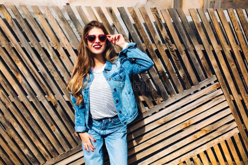 Giovane donna splendida con capelli lunghi che posano davanti al recinto di legno Modello femminile adorabile con la retro attrez fotografia stock libera da diritti
