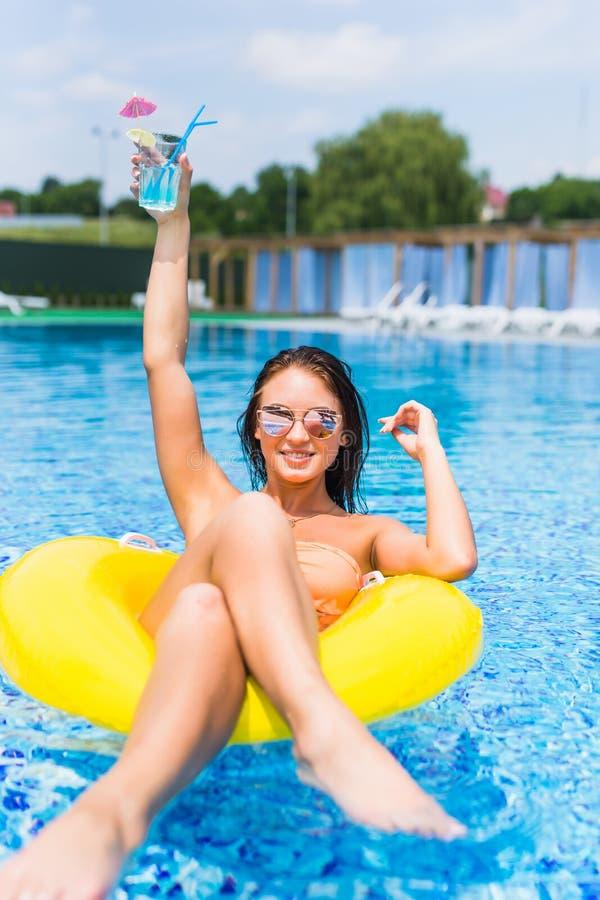 Giovane donna splendida con gli occhiali da sole ed il barattolo con la bevanda fredda che si siede in galleggiante gonfiabile in immagine stock