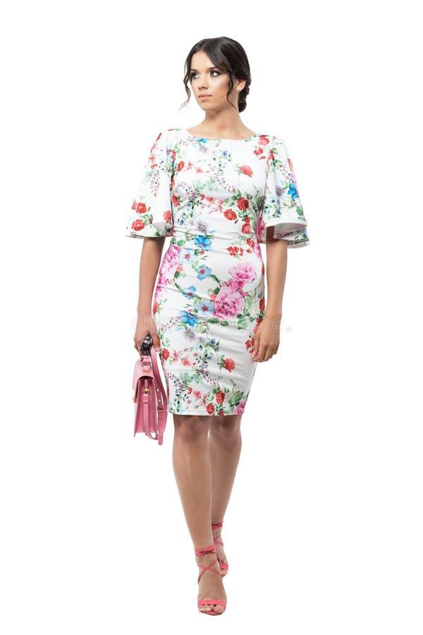 Giovane donna splendida nel distogliere lo sguardo rosa di trasporto di camminata della borsa del vestito floreale da estate immagini stock