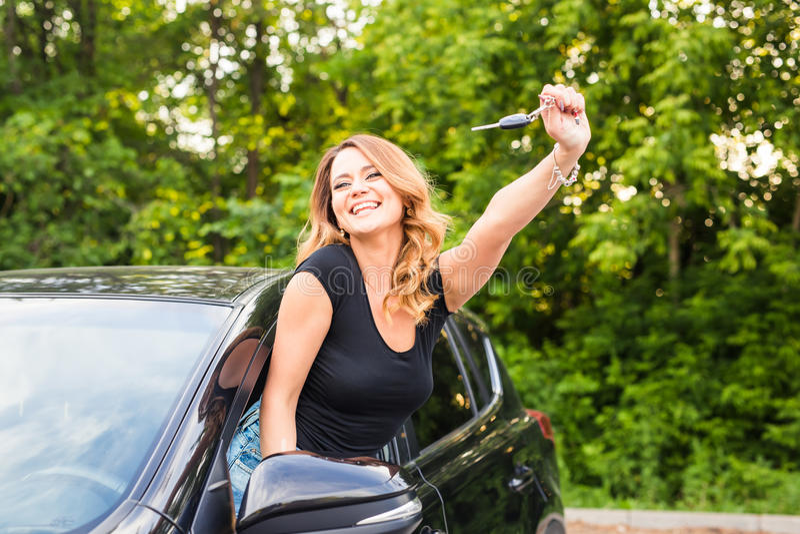 Giovane donna splendida sorridente allegra allegra che ostacola le chiavi alla sua prima nuova automobile Soddisfazione del clien fotografia stock libera da diritti