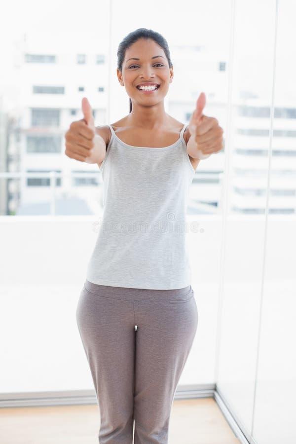 Giovane donna sportiva allegra che dà i pollici su fotografie stock