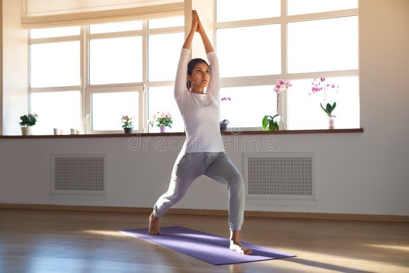 Giovane donna sportiva attraente che fa yoga in una stanza soleggiata luminosa, fotografie stock
