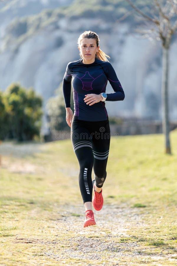 Giovane donna sportiva che corre sulla montagna in bella natura immagini stock