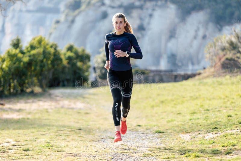 Giovane donna sportiva che corre sulla montagna in bella natura fotografia stock libera da diritti