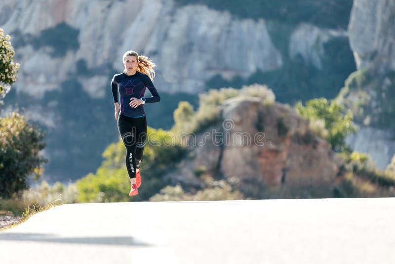 Giovane donna sportiva che corre sulla strada della montagna in bella natura fotografia stock libera da diritti