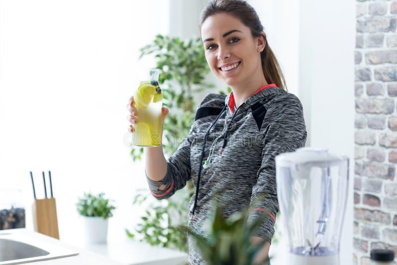 Giovane donna sportiva che esamina macchina fotografica mentre bevendo il succo di limone nel kicthen a casa fotografia stock libera da diritti