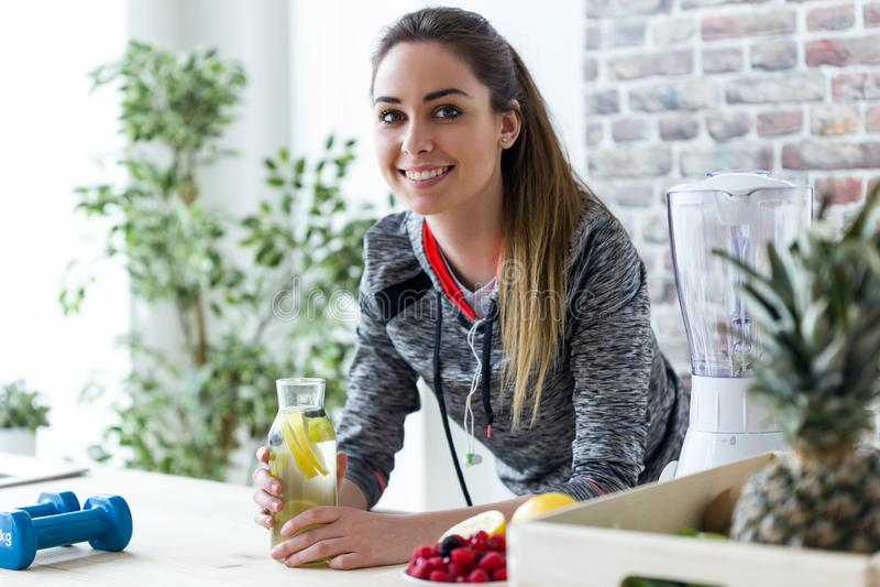 Giovane donna sportiva che esamina macchina fotografica mentre bevendo il succo di limone nella cucina a casa fotografie stock libere da diritti