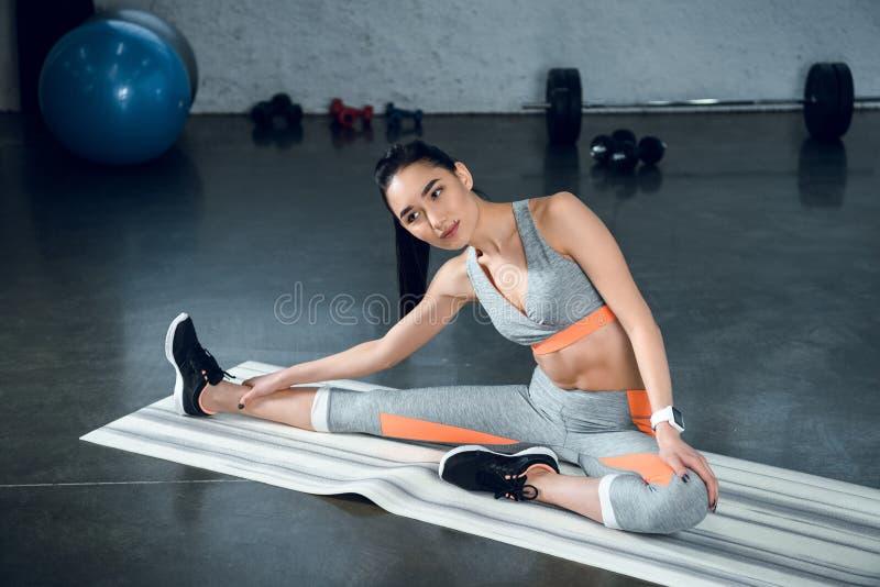 giovane donna sportiva che fa curvatura laterale sulla stuoia di yoga fotografie stock
