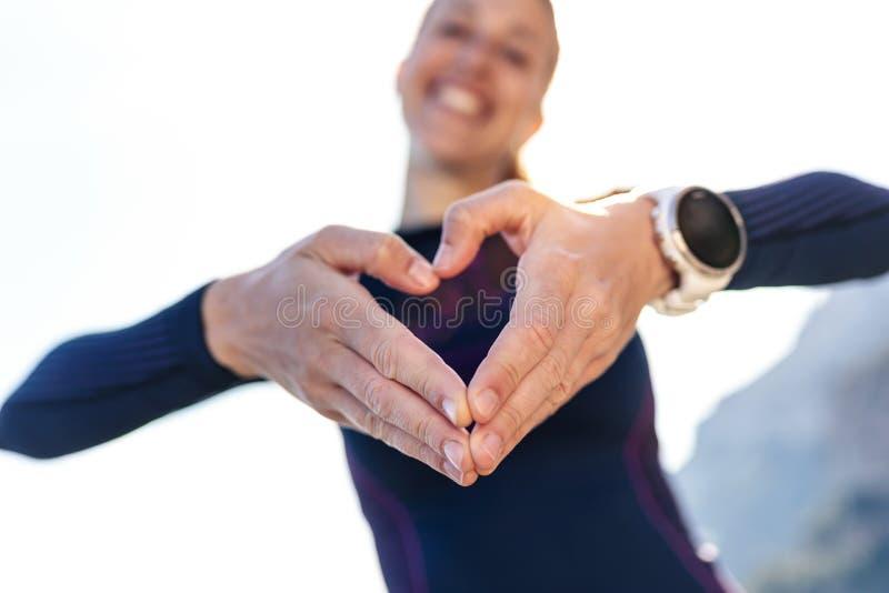 Giovane donna sportiva che fa forma del cuore con le mani mentre posando alla macchina fotografica sulla montagna fotografia stock