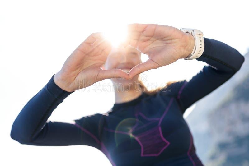 Giovane donna sportiva che fa forma del cuore con le mani mentre posando alla macchina fotografica sulla montagna immagine stock libera da diritti