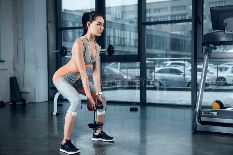 giovane donna sportiva che fa gli edifici occupati con i piatti del peso immagini stock libere da diritti