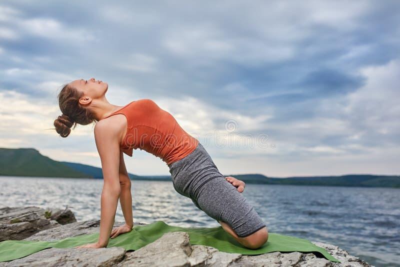 Giovane donna sportiva che fa le varianti differenti della posizione di yoga su un rivershore roccioso fotografia stock