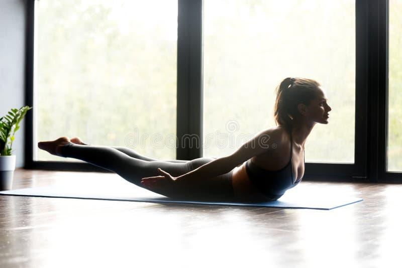 Giovane donna sportiva che fa posa di Salabhasana di yoga fotografia stock