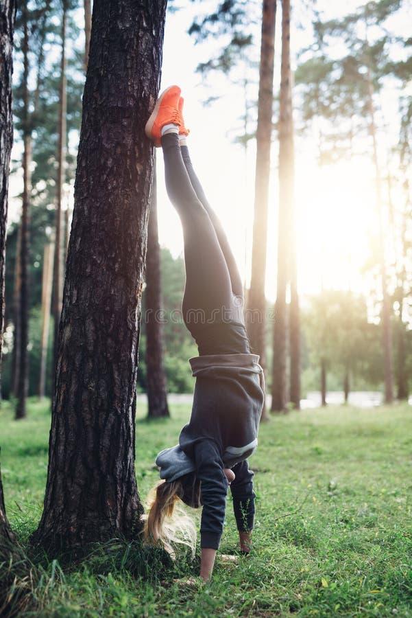 Giovane donna sportiva che fa verticale che pende le gambe diritte sull'albero che pratica nel legno immagini stock