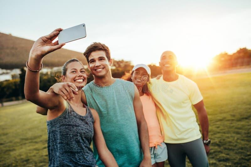 Giovane donna sportiva che prende un selfie con gli amici immagine stock