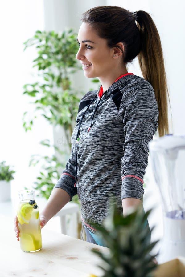 Giovane donna sportiva che sembra obliqua mentre bevendo il succo di limone nella cucina a casa fotografia stock libera da diritti