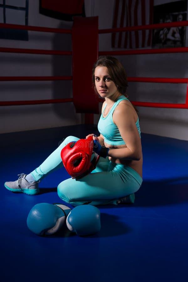 Giovane donna sportiva che si siede vicino ai guantoni da pugile ed al casco di menzogne immagine stock libera da diritti