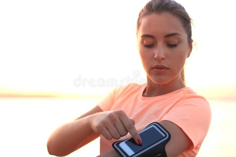 Giovane donna sportiva che sta sulla spiaggia all'aperto al tramonto o all'alba, usi uno Smart Phone toccando il bottone immagine stock