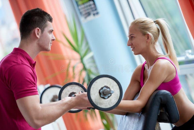 Giovane donna sportiva con il sollevamento di pesi di esercizio dell'istruttore fotografie stock