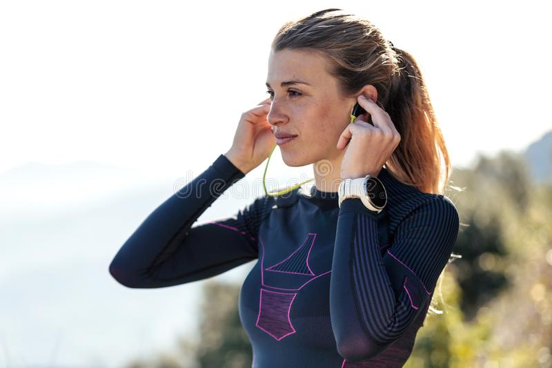 Giovane donna sportiva con le cuffie che preparano per ascoltare la musica alla foresta immagini stock