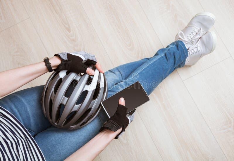 Giovane donna sportiva rilassata che si siede sulla bicicletta della tenuta del pavimento fotografia stock