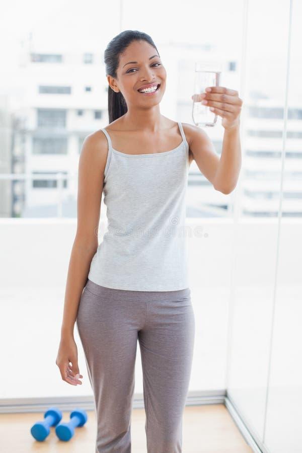 Giovane donna sportiva sorridente che tiene bicchiere d'acqua fotografie stock libere da diritti