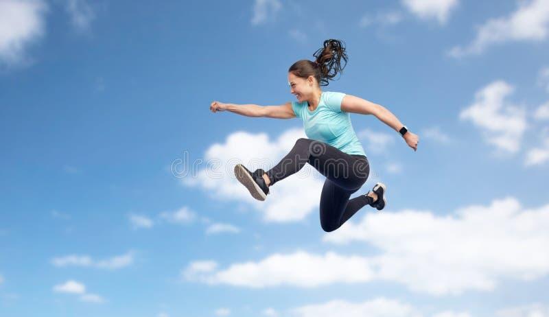 Giovane donna sportiva sorridente felice che salta in cielo fotografia stock libera da diritti