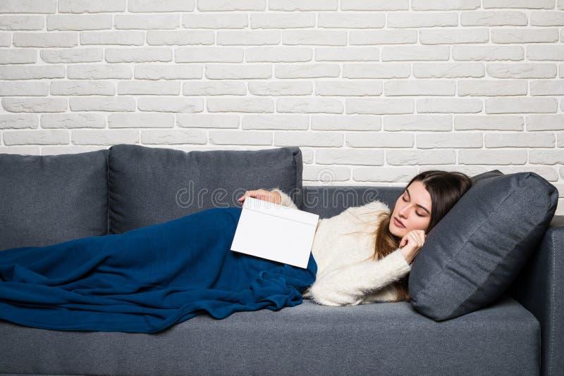 Giovane donna stanca che prende un pelo a casa che si trova su un sofà con un libro che si trova attraverso il suoi petto e lei o immagine stock
