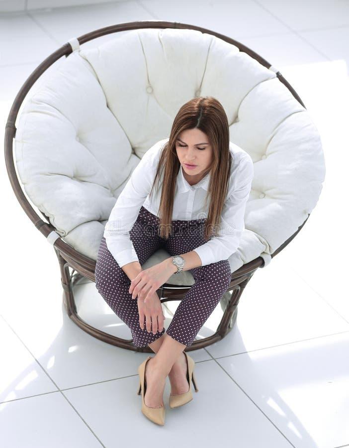 Giovane donna stanca che si siede nella sedia rotonda comoda fotografie stock libere da diritti