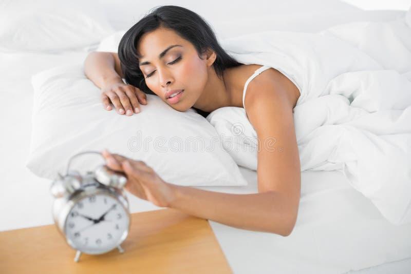 Giovane donna stanca che si trova nel suo sonno del letto fotografia stock