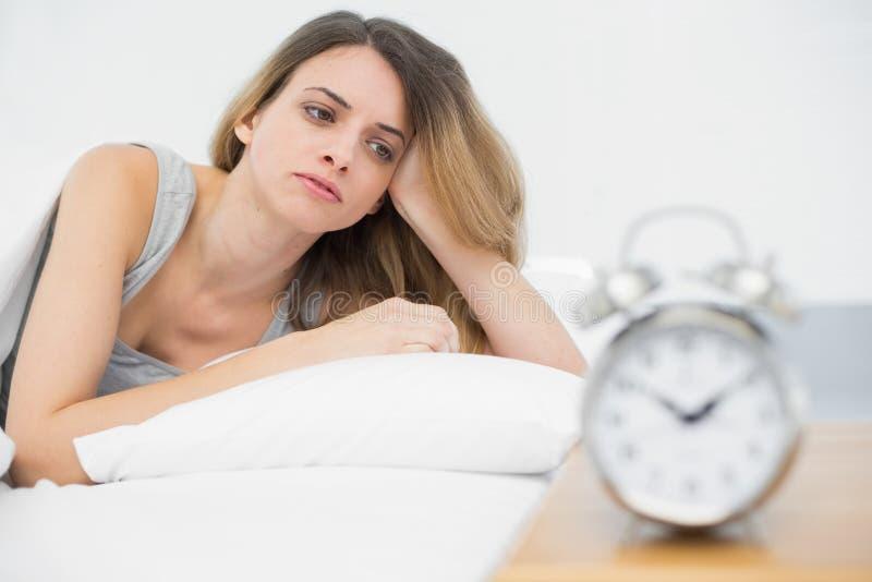 Giovane donna stanca che si trova nell'ambito della copertura sul suo letto immagini stock libere da diritti