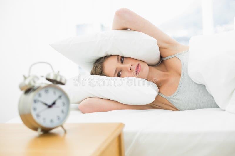 Giovane donna stanca che si trova nella sua copertura di letto le sue orecchie con il cuscino fotografia stock libera da diritti