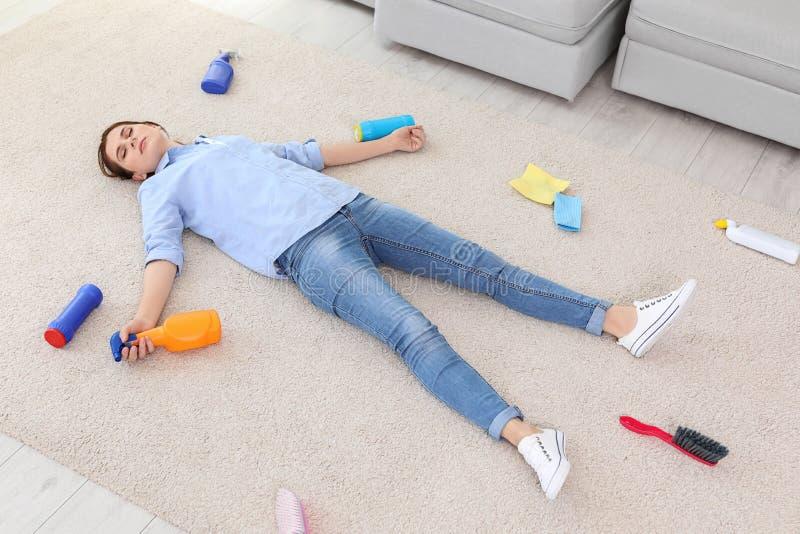 Giovane donna stanca che si trova sul tappeto circondato dai rifornimenti di pulizia fotografia stock libera da diritti
